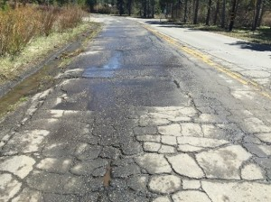 Elks Club road cracked with potholes