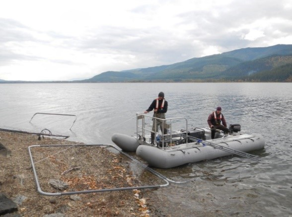 Image shows two people in an inflatebale boat at a lake's shore. The boat has a large square benthic electrode array that the men are preparing for deployment.