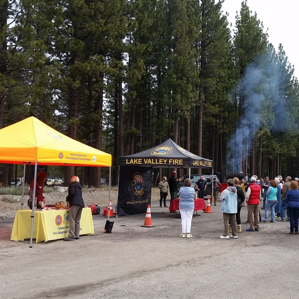 Two outreach booths with people gathered at an evacuation drill
