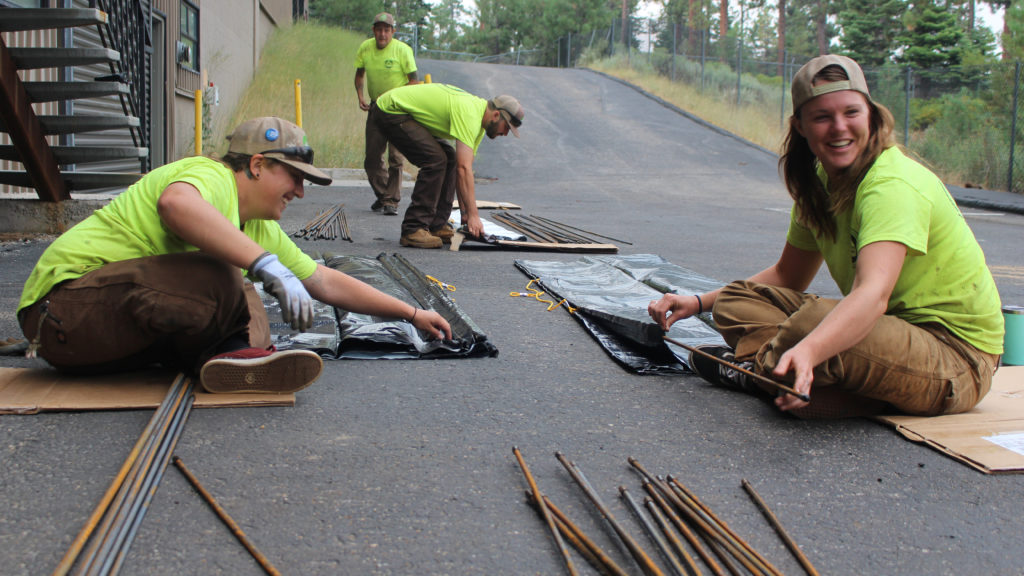 Image shows four people wearing neon yellow shirts working in a parking lot. They are inserting rebar into folded over tarps that we be used as benthic barriers.